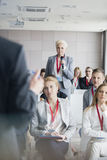 Businesswoman asking questions to public speaker during seminar Royalty Free Stock Image