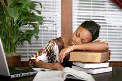 Businesswoman asleep on a stack of books Stock Photo