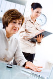 Businesswoman and associate. Senior businesswoman and young assistant working in office Royalty Free Stock Photography