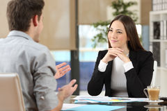 Businesswoman attending a client at office. Businesswoman attending listening to a client who is talking at office Royalty Free Stock Photos
