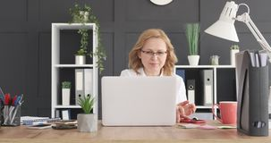 Businesswoman attending mobile phone calls at work. Mature businesswoman attending mobile phone calls at workplace stock footage