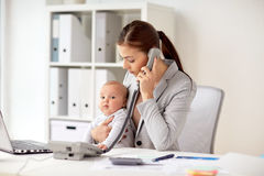 Businesswoman with baby calling on phone at office Royalty Free Stock Image