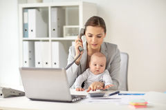 Businesswoman with baby calling on phone at office Stock Photos