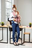 Businesswoman with baby son at the office. Full body portrait of an elegant businesswoman carrying her baby son at the white office Royalty Free Stock Image