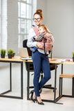 Businesswoman with baby son at the office. Full body portrait of an elegant businesswoman carrying her baby son at the white office Royalty Free Stock Photo