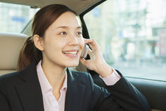 Businesswoman in Back Seat of Car on the Phone Royalty Free Stock Photo