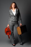 A businesswoman with a bag and a suitcase. Stock Image
