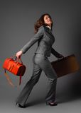 A businesswoman with a bag and a suitcase. Royalty Free Stock Photography