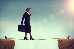 Businesswoman balancing on a tightrope Royalty Free Stock Image