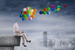Businesswoman with balloon head on rooftop Royalty Free Stock Photography