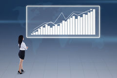 Businesswoman and bar chart on blue world map Royalty Free Stock Photography