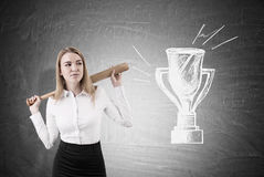 Businesswoman with baseball bat and champion cup Stock Photos