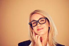 Businesswoman beaming with pleasure. Attractive blonde businesswoman in glasses beaming with pleasure on a light brown background with copyspace Stock Photography