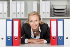 Businesswoman Behind Binders Sitting At Desk Stock Image