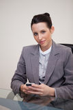 Businesswoman behind desk with cellphone Royalty Free Stock Photography