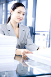 Businesswoman behind a desk with paperwork Stock Image
