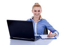 Businesswoman behind the desk writing Stock Photos