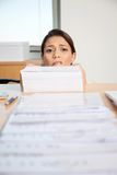 Businesswoman Behind Pile Of Paper. Head of businesswoman behind large pile of papers Stock Images