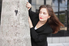 Businesswoman behind a tree Royalty Free Stock Image