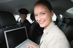 Businesswoman being chauffeured while working. In the car Royalty Free Stock Photos