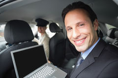 Businesswoman being chauffeured while working. In the car Stock Image