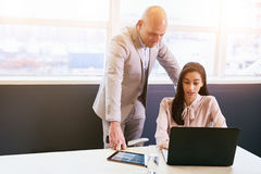 Businesswoman being supervised by her male superior while working Stock Image