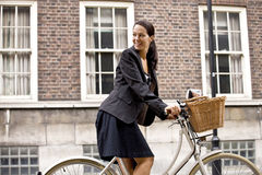A businesswoman on a bicycle, smiling Stock Photo