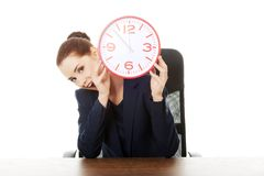 Businesswoman with big clock at the office Stock Photography