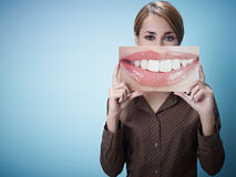Businesswoman with big mouth. Mid adult business woman holding photo of toothy smile on blue background. Horizontal shape, front view, waist up, copy space Royalty Free Stock Image