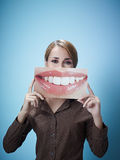 Businesswoman with big mouth. Mid adult business woman holding photo of toothy smile on blue background. Vertical shape, front view, waist up, copy space Stock Photos