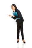 Businesswoman with binder pointing to the left Royalty Free Stock Photo