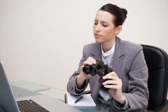Businesswoman with binoculars on her desk Royalty Free Stock Photos