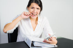 Businesswoman biting her pen in frustration. Businesswoman with a distraught expression biting her pen in frustration, worry or anger as she sits at her desk Royalty Free Stock Photography