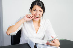 Businesswoman biting her pen in frustration. Businesswoman with a distraught expression biting her pen in frustration, worry or anger as she sits at her desk Stock Photo