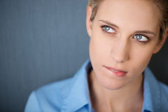 Businesswoman Biting Lip While Looking Away Against Grey Wall Stock Photography
