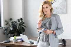 Businesswoman biting pencil. And looking away stock image