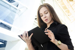 Businesswoman in black clothes with long hair flips a black notebook. A young businesswoman in black clothes with long hair flips a black notebook. Gold watch is Royalty Free Stock Photo