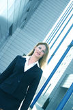 Businesswoman In Black Suit Angled Blue Tint. Portrait of a businesswoman in a black suit standing outside of office buildings.  Vertical shot at an angle.  Blue Royalty Free Stock Photo