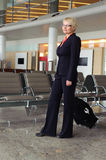 Businesswoman in black suit with luggage Royalty Free Stock Images