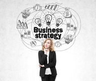 Businesswoman in a black suit standing near a concrete wall with a business strategy drawing on it. Stock Images