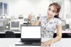 Businesswoman with blank laptop monitor. Young businesswoman hold thumb up while showing blank laptop monitor in office stock photo