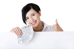 Businesswoman with blank sign board holding money. Royalty Free Stock Image