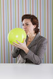 Businesswoman blowing a balloon Stock Photos