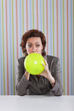 Businesswoman blowing a balloon Royalty Free Stock Images