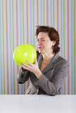 Businesswoman blowing a balloon Royalty Free Stock Image