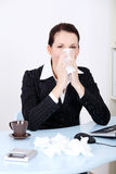 Businesswoman blowing her nose. Royalty Free Stock Image