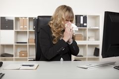 Businesswoman blowing her nose at her desk Stock Photo