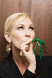 Businesswoman blowing party blower Stock Images