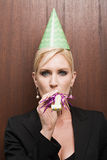 Businesswoman blowing party horn blower Royalty Free Stock Image