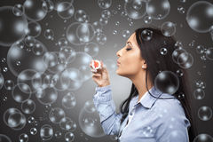 Businesswoman blowing soap bubbles Stock Photos